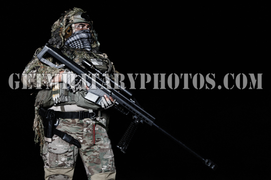 Army sniper with big rifle standing
