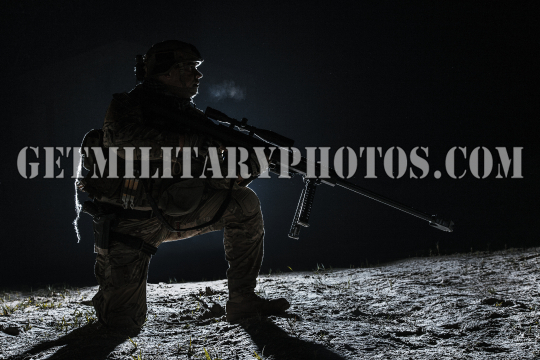 Army sniper with big rifle sitting holding rifle